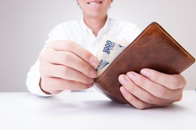 財布からお金を取り出す男性
